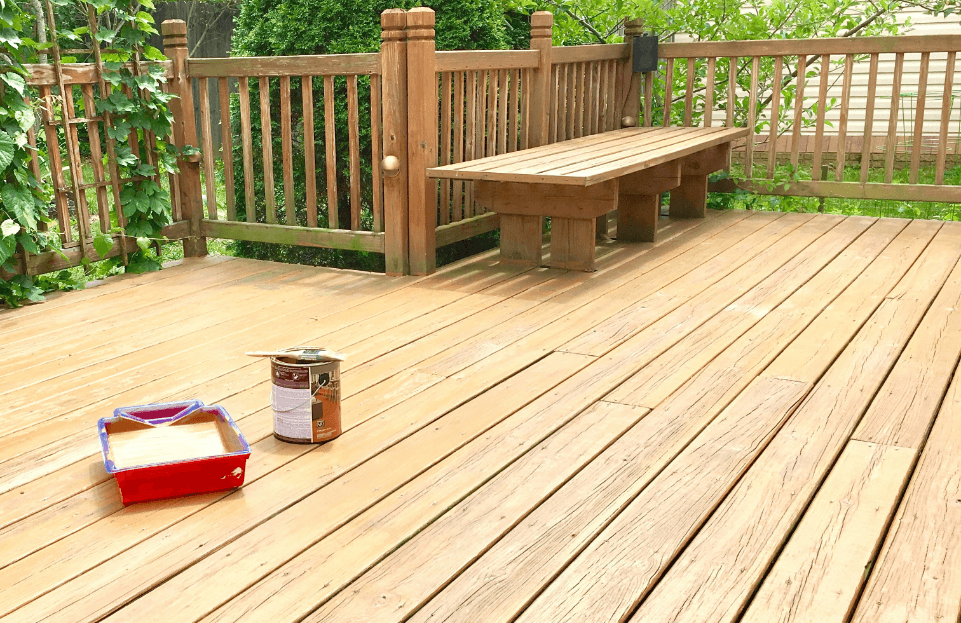 freshly stained deck with a painted fence
