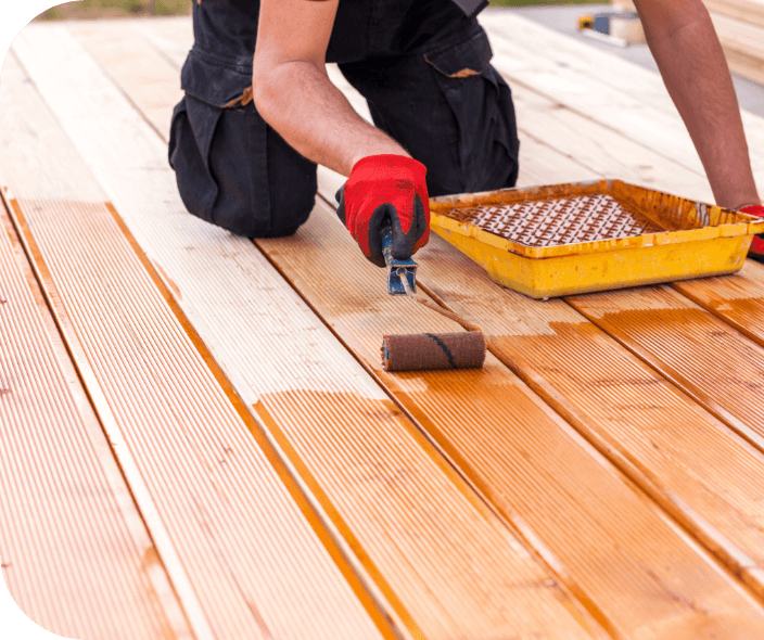 a painting professional applying stain to a deck