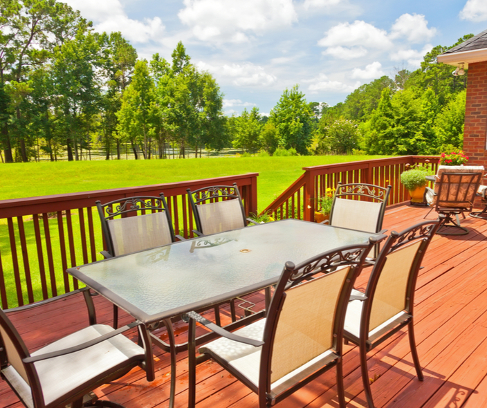 a stained deck and fence overlooking a backyard